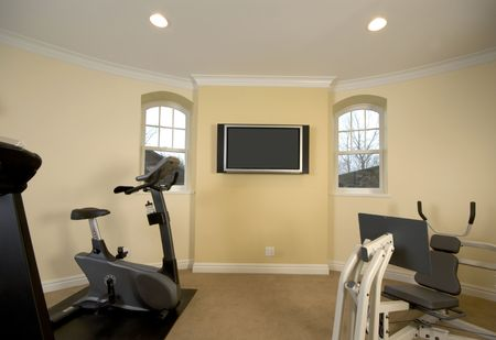 recreation: home gymnasium with televison in mansion private residence Stock Photo