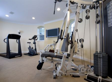home gymnasium with televison in mansion private residence Stock Photo