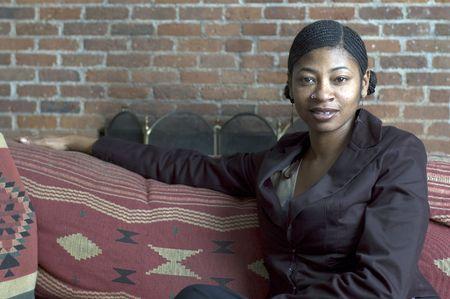 invitando: Hermosa mujer de negro con sof� invitando a sonre�r