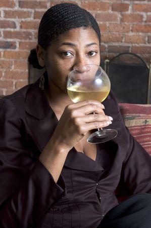beautiful black woman on sofa with glass of wine photo