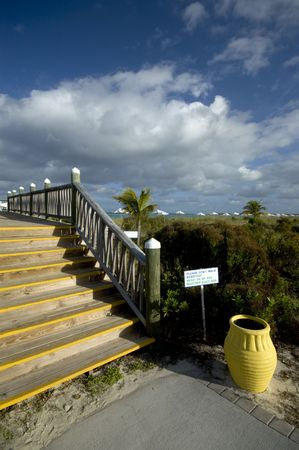 don't walk barefoot sign  boardwalk yellow urn by the beach caribbean sea Stock Photo - 735723