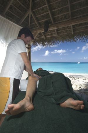 woman middle age: woman middle age relaxing with professional massage at resort by the sea