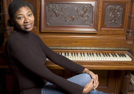 beautiful black woman with old grand upright piano