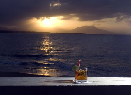 cocktail by the sea at sunset with island in distance photo