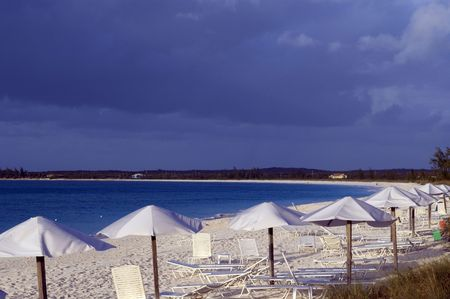 beautiful blue water beach with umbrellas lounge chairs at resort photo