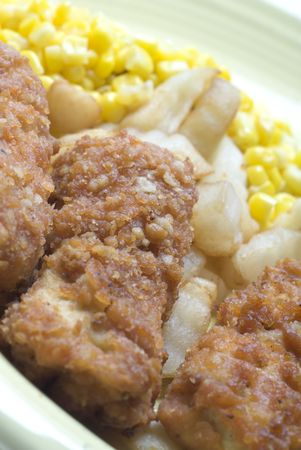 chicken patties strips fried with corn and french fried potatoes photo