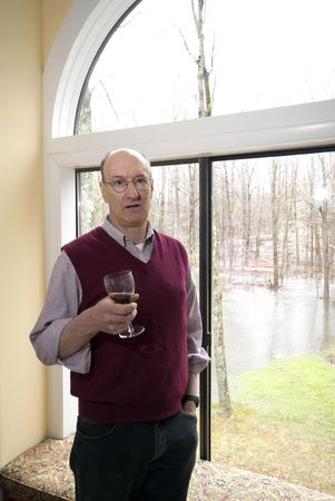 man in house by picture window with flood in backyard after storm drinking wine