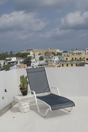flat roof: lounge chair on deck of luxury condo with rooftops of old san juan showing san juan cathedral puerto rico Stock Photo