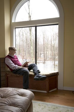 picture window: suburban man reading book flooded backyard Stock Photo