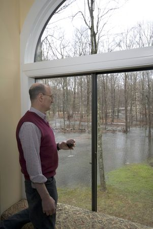 suburban man looking at flooded backyard drinking wine