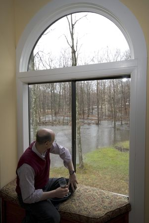 suburban man looking at flooded backyard drinking wine photo