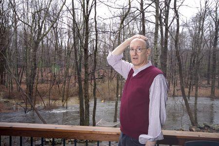 suburban man looking at flooded backyard upset