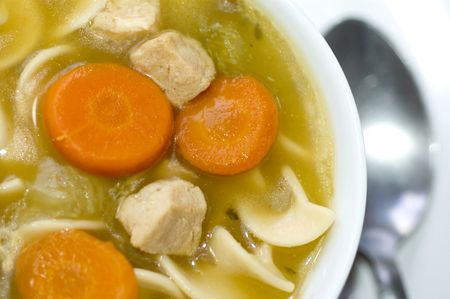 rotini: turkey noodle soup with carrots in bowl macro
