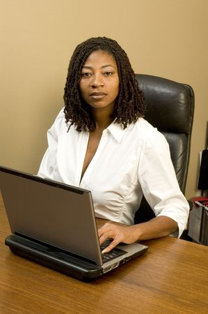 attractive black woman in office working computer braided hair Stock Photo