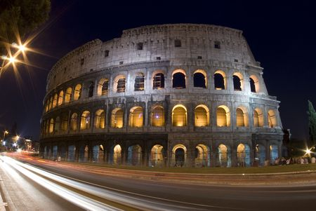 colosseum rome italy night time with car light streaks tourists photo