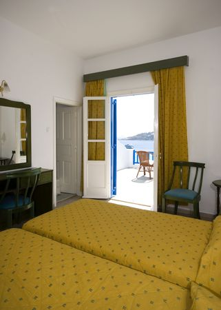 suite: greek island hotel suite room with view of beach and cyclades architecture from hotel suite patio Stock Photo