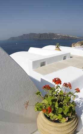 cycladic: santorini classic greek island architecture houses over the sea with flowers cyclades