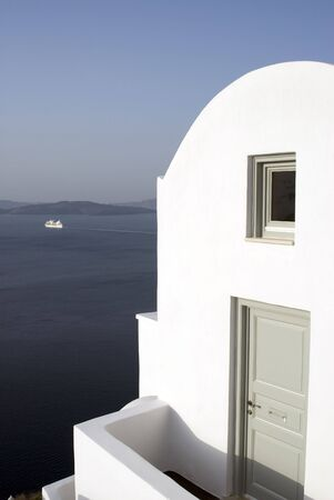 famous industries: santorini villa hotel over sea with view of cruise ship in harbor greek islands Stock Photo