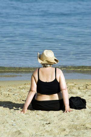 Chubby zware vrouw op strand met hoed