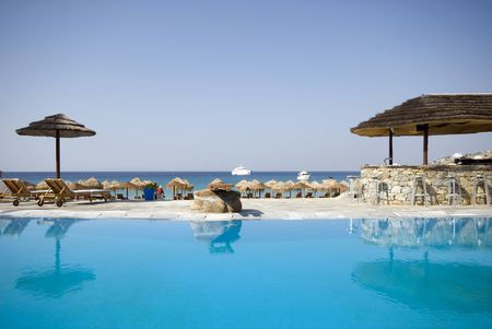 swimming pool by sea at resort hotel luxurious greek island with stone bar photo
