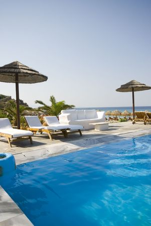 swimming pool by sea at resort hotel luxurious greek island photo