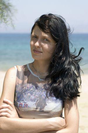 pretty young woman smiling thoughtful greek island beach photo