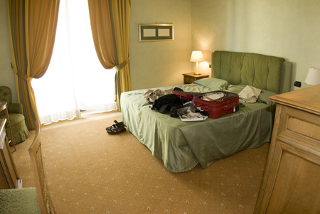 messy: hotel suite room with  suitcase open and clothes and equipment on bed messy