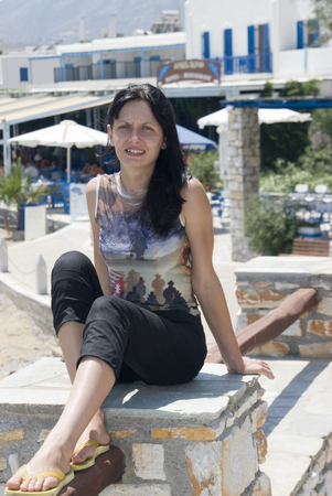 attractive young woman with slight smile sitting near greek island  beach