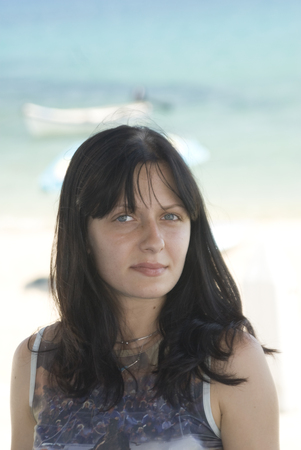attractive young woman with slight smile beach and boats in background Banco de Imagens