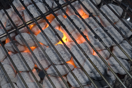 flaming hot charcoal briquets in a kettle grill