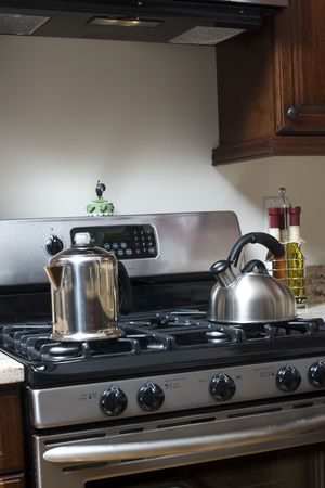 appliance: stainless steel stove with coffee pot and tea pot in kitchen Stock Photo