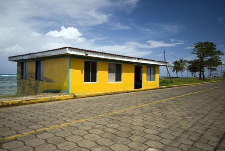bright yellow business building caribbean seaside cobble stone road corn island nicaragua Reklamní fotografie