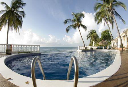 luxury infinity swimming pool with raft float caribbean sea resort hotel with palm trees nicaragua Фото со стока