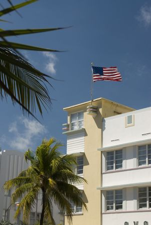 artdeco: architecture art deco hotel facade south beach miami florida with palm tree and american flag blowing in the wind