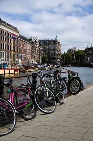 typical bicycles commuter canal old building amsterdam holland the netherlands