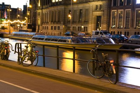 streetscene: bicycles canal cruise boats and architecture at night amsterdam holland