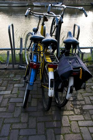 commuter bicycles parked by canal amsterdam typical street scene holland netherlands europe Stock Photo - 3300904