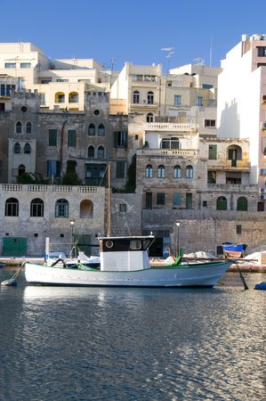 classic old fishing boat in harbor malta with generic architecture mediterranean europe photo