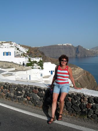 ia: middle age female lady tourist smiling  hotel view traditional  with volcanic cliff caldera view greek islands greece santorini thira ia oia town