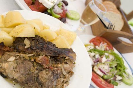 specialit�: agnello in carta cena con insalata greca insalata di polpo vino isola greca Taverna ristorante di specialit� Archivio Fotografico