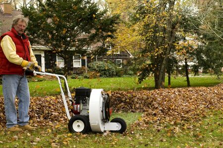 homeowner using leaf blower professional push style with pile of leaves suburban home in the autumn photo