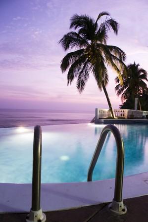 luxury infinity swimming pool resort at sunset sundown purple sky caribbean nicaragua central america Фото со стока