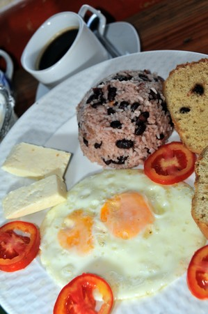corn island: breakfast Nicaragua rice beans called gallo pinto with eggs cheese and coconut bread with tomatoes and coffee