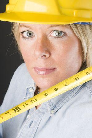 pretty blond female construction worker contractor builder hard hat helmet head shot measuring ruler tool photo