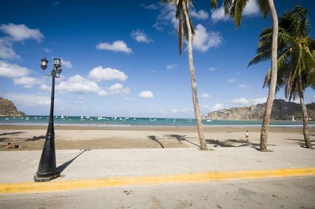 lampost: malecon boardwalk beach bay on pacific ocean busy developing tourist destination of san juan del sur nicaragua with famous  face of indian indio on mountain