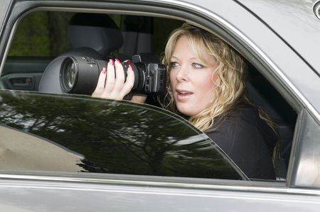 female private investigator or spy or secret agent taking photographs from car
