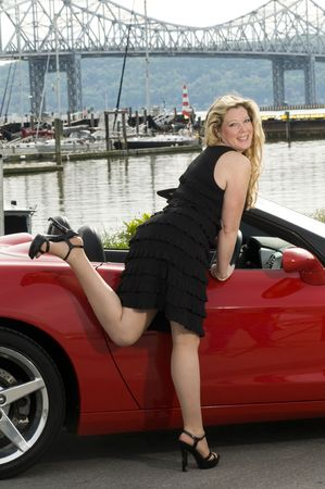 sexy woman with red sports car by a yacht club on the  hudson river new york photo