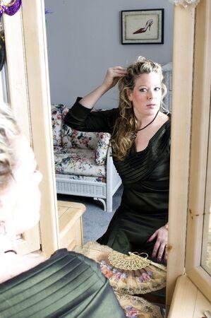 pretty woman fashion model applying makeup in front of triple mirror