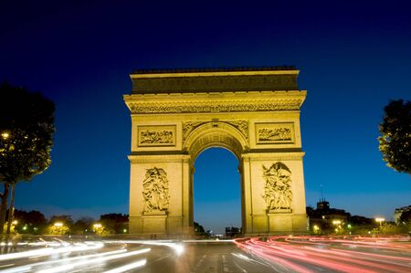 charles de gaulle: arc de triomphe arch of triumph at night with car streaks in the center of the Place Charles de Gaulle also known as Place del Etoile in Paris France on the Champs-Elysees Stock Photo