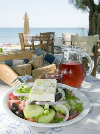 mediterranean home: carafe of home made house rose wine and greek salad with feta cheese at greek island taverna with crusty local bread photographed in the greek islands